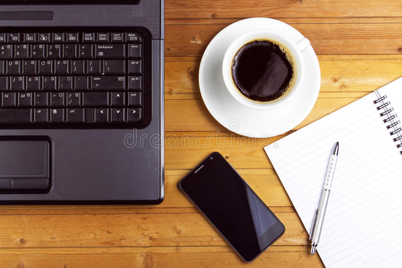 Laptop, tablet ,smartphone with financial documents on wooden table royalty free stock photos