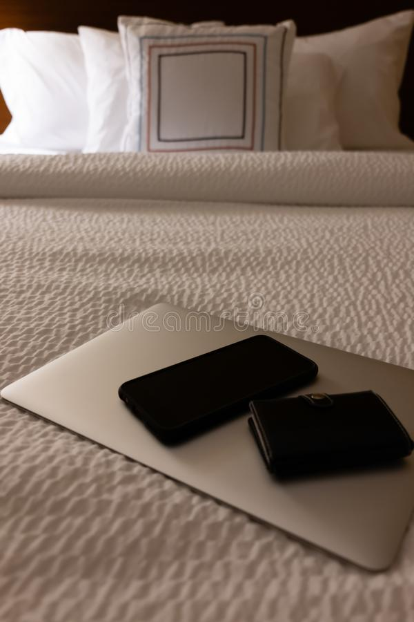 Laptop, Telefon und Geldbörse auf Hotelbett lizenzfreie stockfotografie