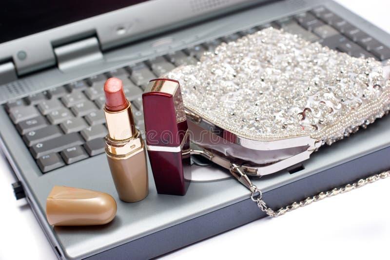 Laptop toetsenbord met lippenstiften en zilveren zak stock afbeeldingen
