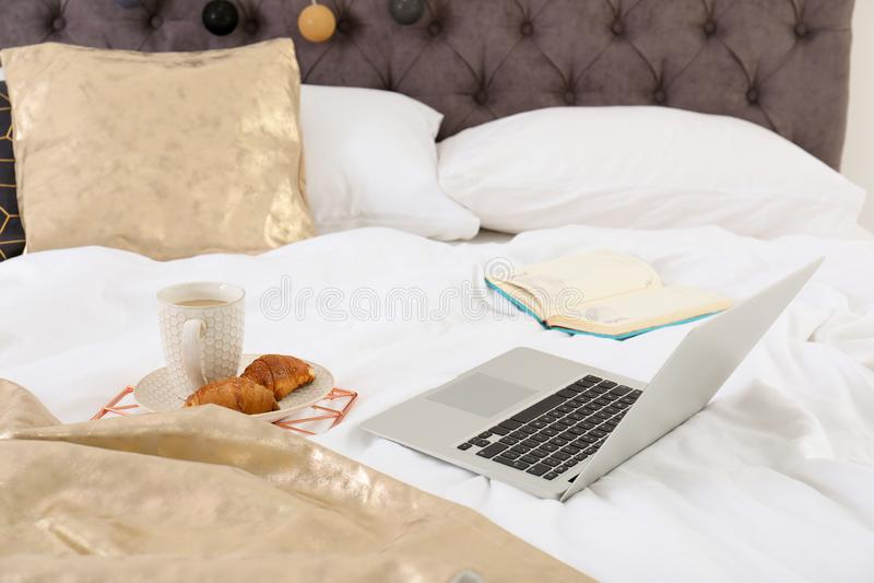 Laptop und Frühstück auf Bett lizenzfreie stockbilder
