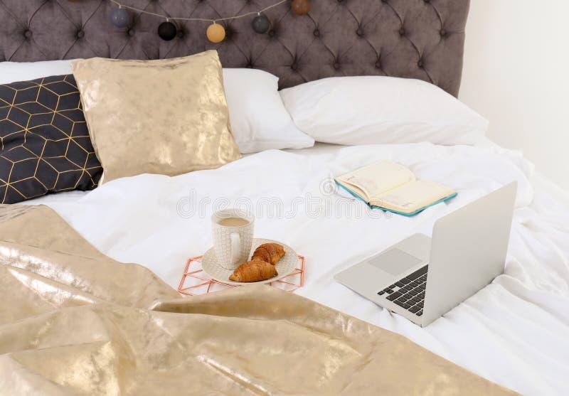 Laptop und Frühstück auf Bett stockbild