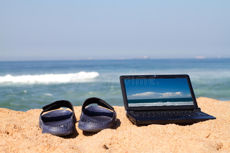 Laptop und Sandelholze auf Strand stockbilder