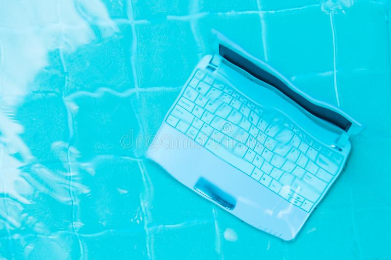 Laptop under water. Minicomputer at the bottom of the pool. The concept of obstruction at work. Blur abstract background royalty free stock image
