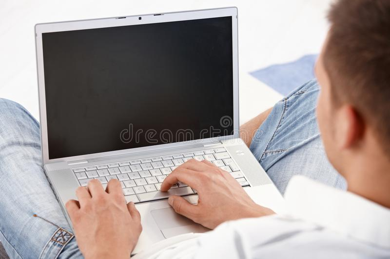 Laptop in use. Young man holding laptop in lap, working on it, photographed from behind