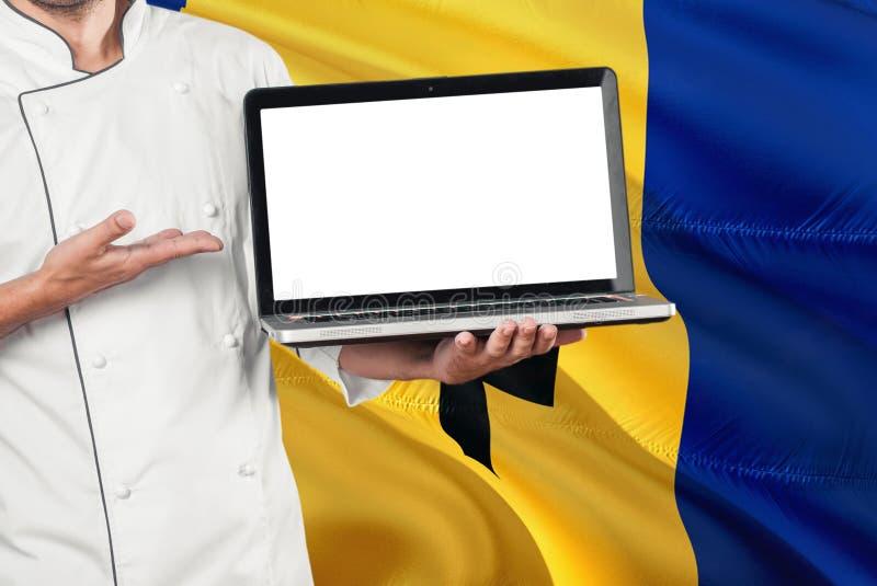 Laptop van Barbados van de Chef-kokholding met het lege scherm op de vlagachtergrond van Barbados Kok eenvormig dragen en het ric stock foto