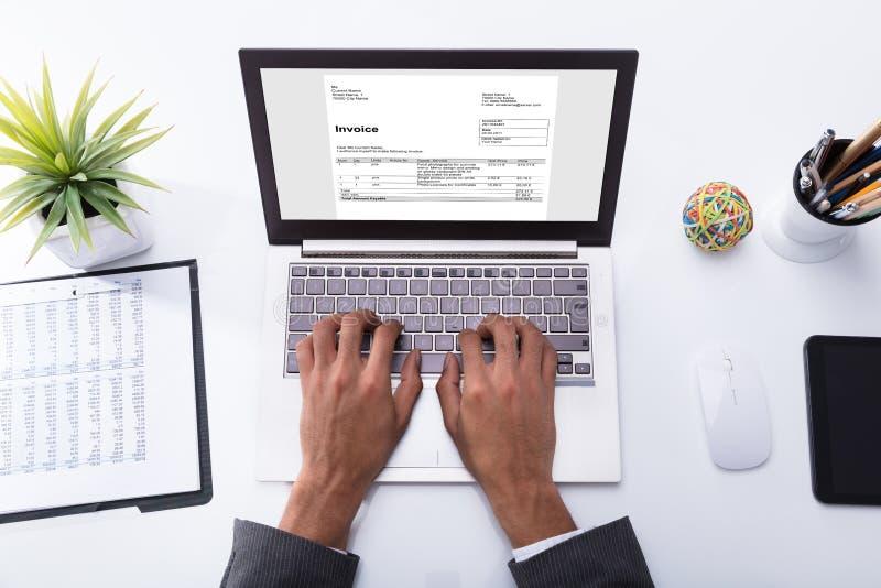 Laptop van Businesspersonchecking invoice on stock afbeelding