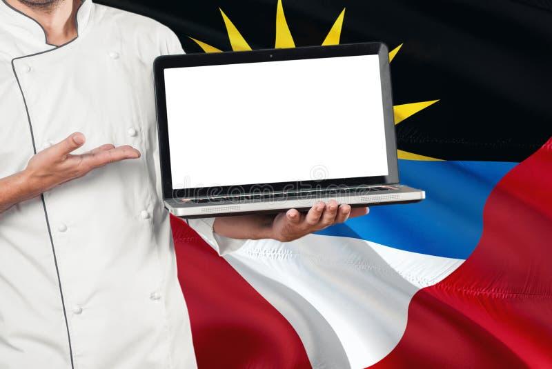Laptop van de chef-kokholding met het lege scherm op Antigua en de vlagachtergrond van Barbuda Kok eenvormig dragen en het richte royalty-vrije stock fotografie