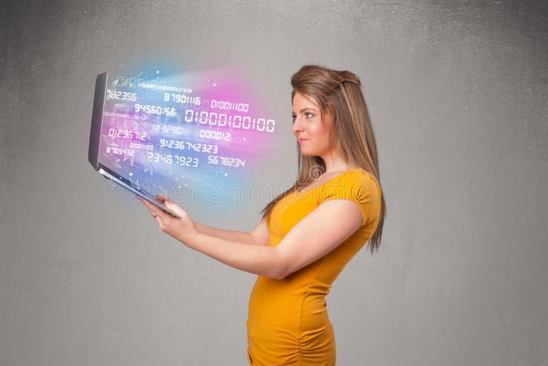 Laptop van de vrouwenholding met het exploderen gegevensandnumers royalty-vrije stock afbeelding