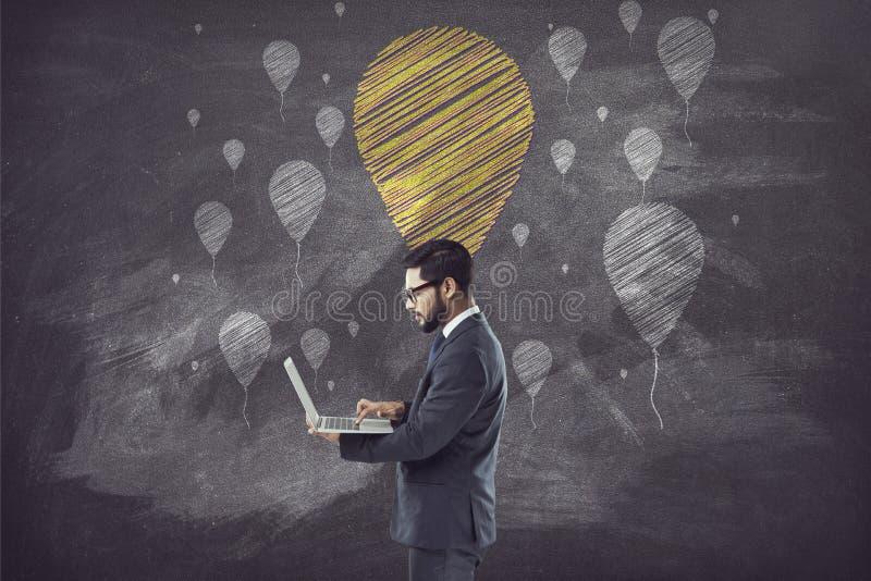 Laptop van de zakenmanholding voor bord met ballon royalty-vrije stock fotografie