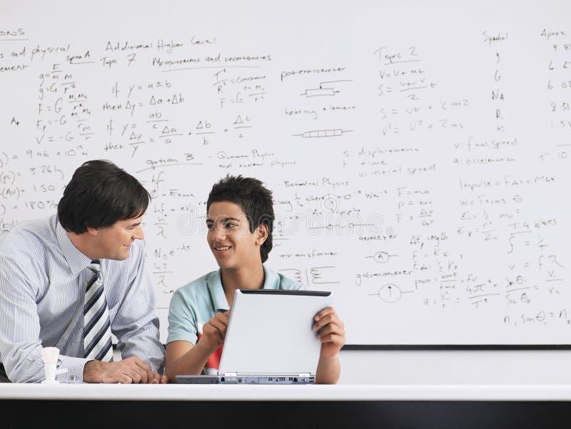 Laptop van leraarsand student using in Klasse stock foto