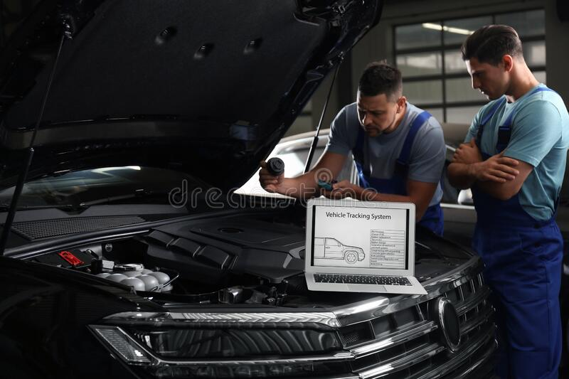 Laptop with vehicle tracking system and blurred mechanics on background stock photography