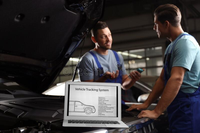 Laptop with vehicle tracking system and mechanics on background. Auto diagnostic royalty free stock photos