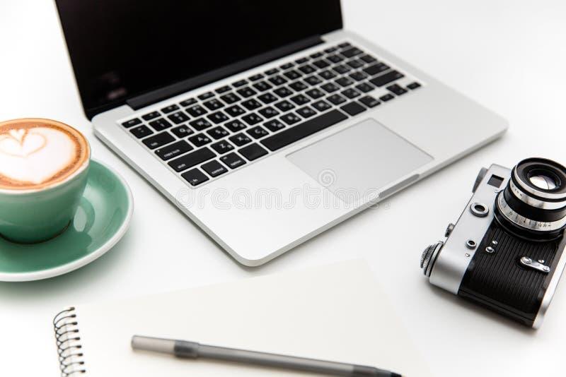 Laptop, Weinlesekamera, Tasse Kaffee, Notizblock und Stift lizenzfreies stockfoto