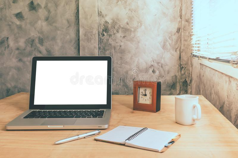Laptop with white blank screen and cup of coffee,notebook,pen and clock on the wooden desk with grunge wall background. stock photos