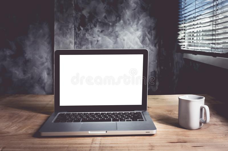 Laptop with white blank screen and cup of coffee on the wooden desk with grunge wall background. Lifestyle Concept royalty free stock image