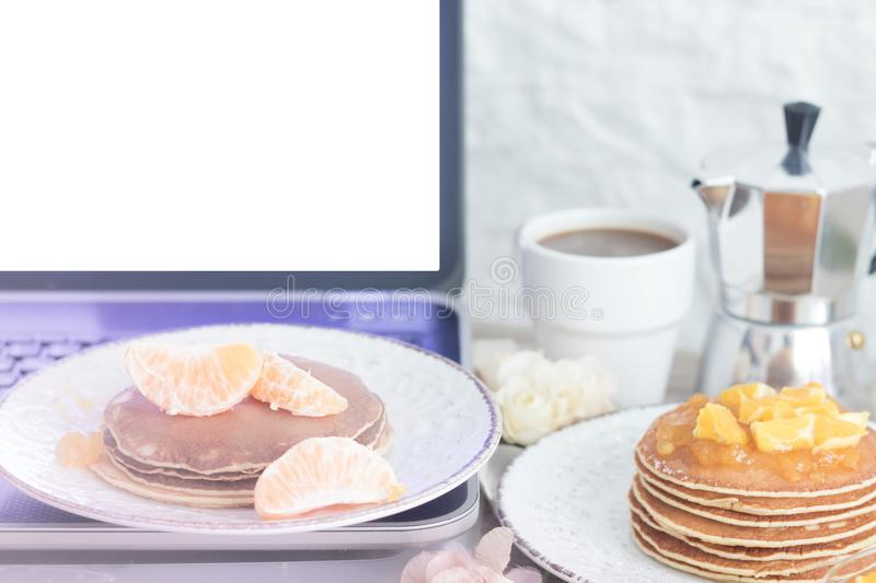 Workplace. Laptop with blank screen on table with breakfast: pancakes and coffee. Front view. Copy space royalty free stock photos