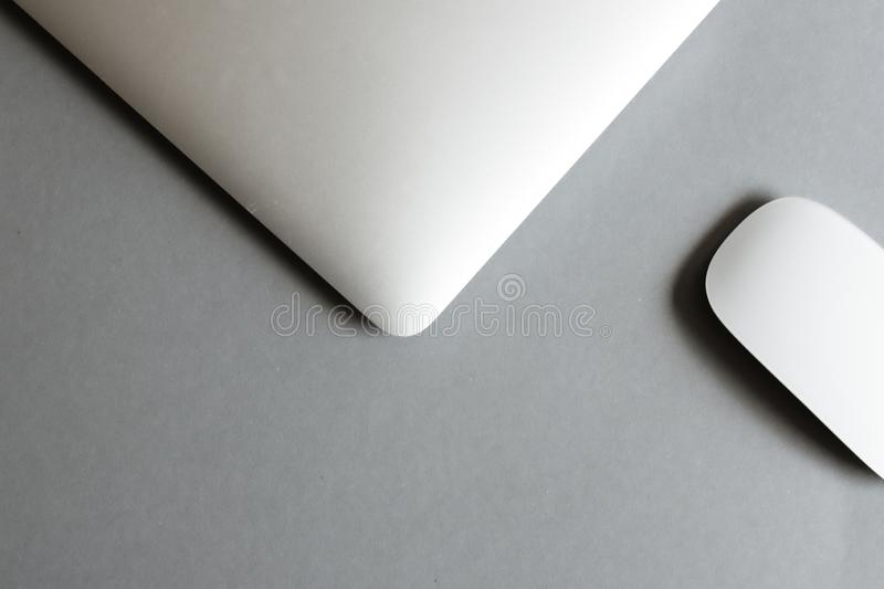 Laptop and wireless mouse on table royalty free stock photography