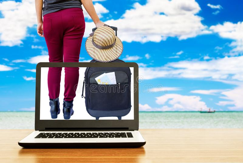 Laptop with woman holding suitcase. On beautiful sea background, travel concept royalty free stock photography