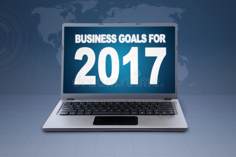 Laptop with world map background. Picture of laptop computer showing text of business goals for 2017 on the monitor with world map background royalty free stock image