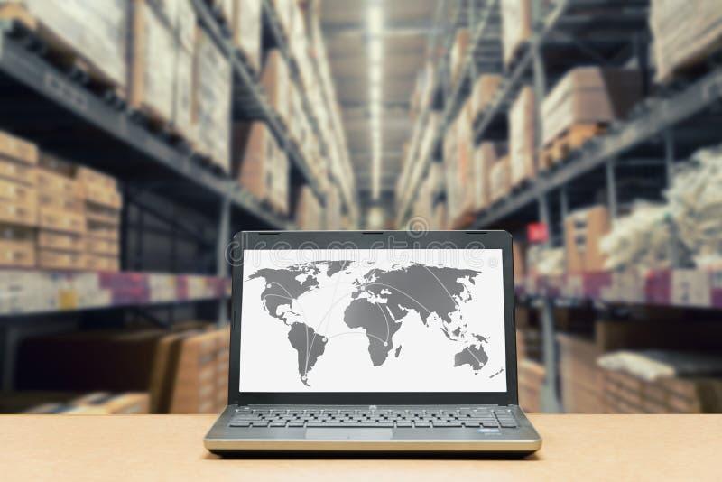 Laptop z białym pustym ekranem z globalną mapą na brown drewnianym d obrazy stock