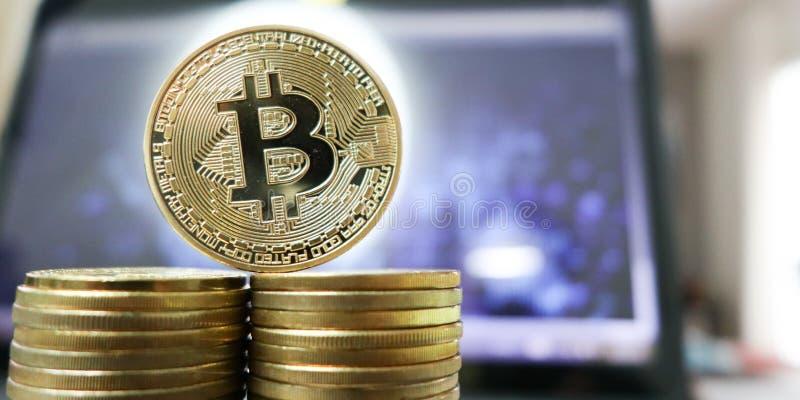 Laptop z Bitcoin mapą na ekranie wśród stosów Bitcoins handel zdjęcia stock