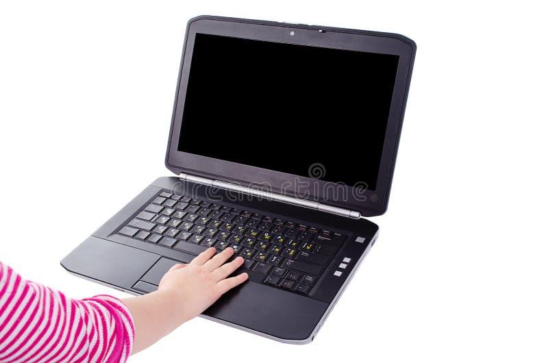 Laptop z dziecka ręką na klawiaturze na białym tle zdjęcie royalty free