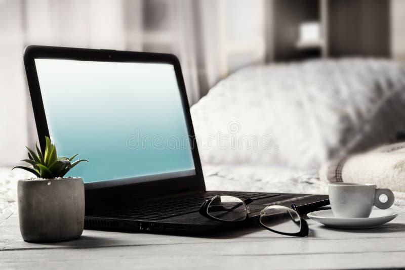 Laptop z pustym ekranem obok szkieł i filiżanka kawy na wezgłowie stole w sypialni zdjęcia royalty free