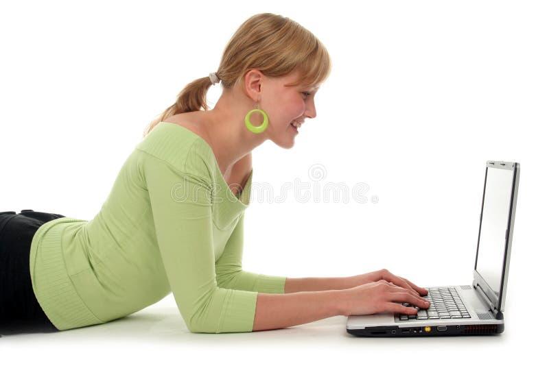 laptopa na leżące przy użyciu kobiety obrazy stock