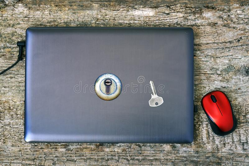 Laptope cerrado con una cerradura de puerta y una llave en la tapa que miente en la tabla de madera Concepto personal de la segur imagen de archivo