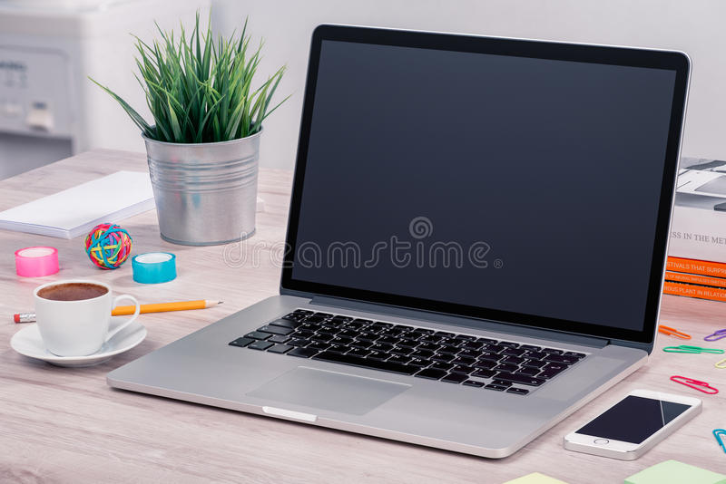 Laptopmodell auf Schreibtisch mit Smartphone und Tasse Kaffee stockfoto