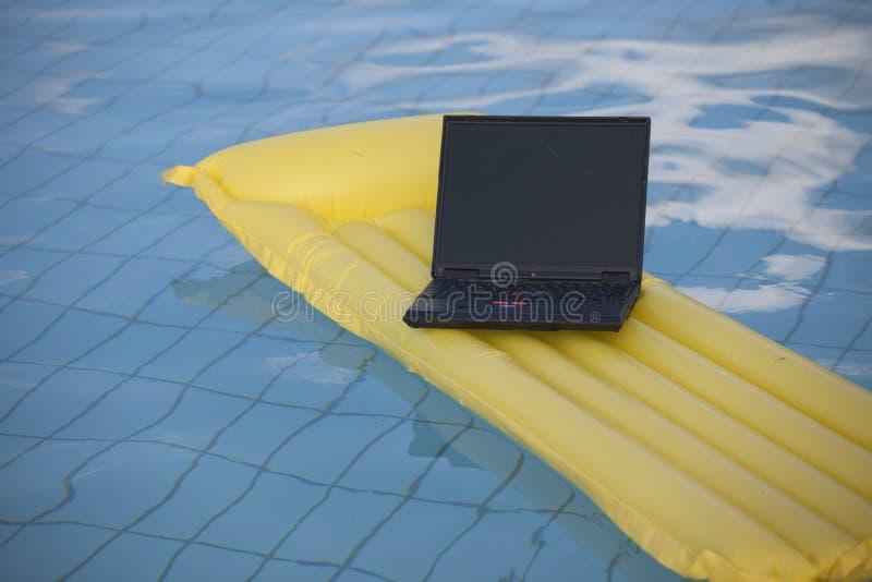 Laptopschwimmen im Pool stockbilder