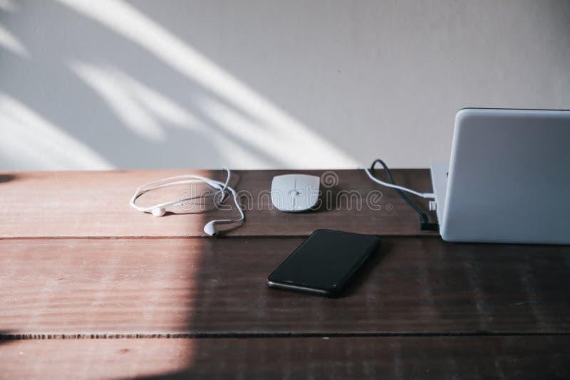 Laptoptoetsenbord op een robuust, houten tafel Mengsel van kantoorbenodigdheden en gadgets op een houten bureauachtergrond royalty-vrije stock afbeeldingen