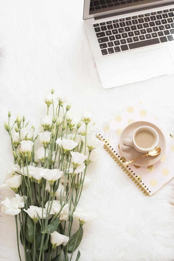 Laptopu, kawy, notatnika i wielkiego bukieta biali kwiaty na podłoga na białym futerkowym dywanie, Freelance mody wygodny femin zdjęcia royalty free