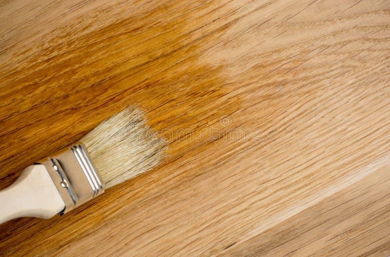 Laque d'espace libre de peinture de brosse d'utilisation de main de plan rapproché sur la surface en bois photo libre de droits