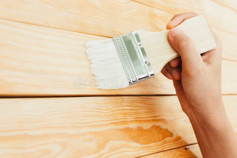 Laque de peinture de brosse d'utilisation de main de plan rapproché sur la surface en bois photographie stock libre de droits
