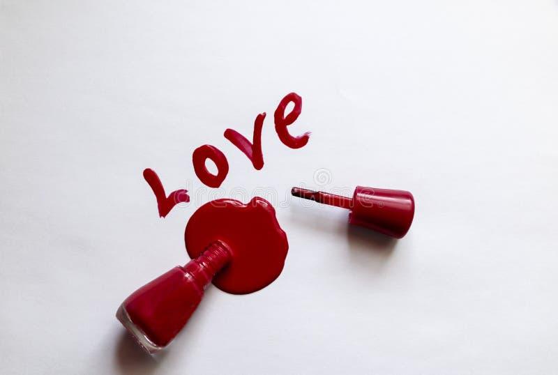 Laque rouge Amour - écrit dans le vernis à ongles rouge sur un fond blanc Billette pour une carte postale - vacances de lacomanya photos stock