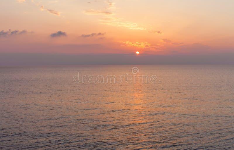 Laranja de giro do céu O sol que estabelece no mar Nuvens e ondas que encontram-se acima no oceano Atividade do desenrolamento na imagem de stock royalty free