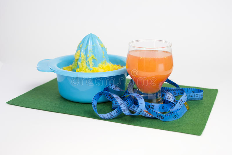 Laranja e suco de toranja recentemente espremidos no vidro transparente com juicer e medidor do citrino no guardanapo verde no ba imagens de stock