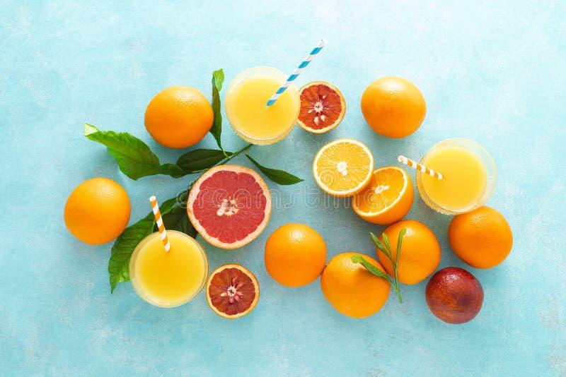 A laranja e a toranja espremeram recentemente o suco nos frutos de vidro e frescos em um fundo vívido azul foto de stock