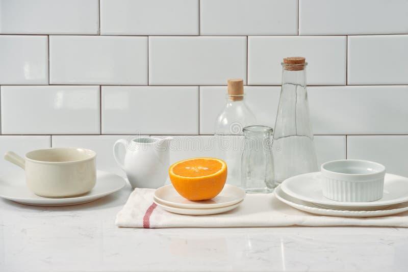 Laranja em um prato na tabela na cozinha fotografia de stock