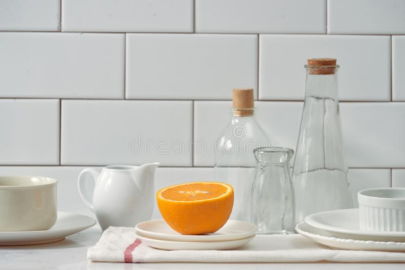 Laranja em um prato na tabela na cozinha imagem de stock