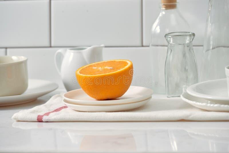 Laranja em um prato na tabela na cozinha foto de stock