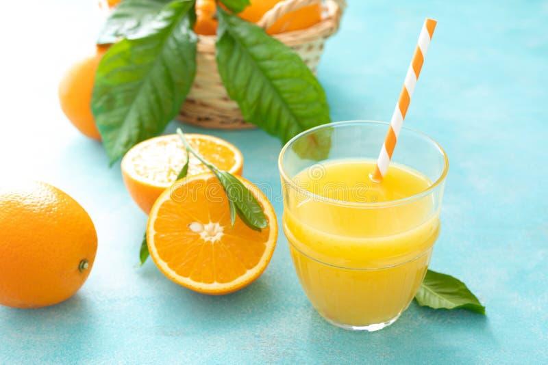 A laranja espremeu recentemente o suco nos frutos de vidro e frescos imagens de stock royalty free