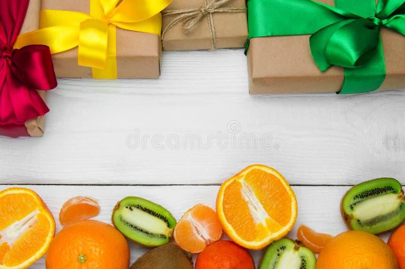 A laranja, a tangerina e a caixa de presente do fruto com fita curvam-se no fundo retro de madeira branco foto de stock