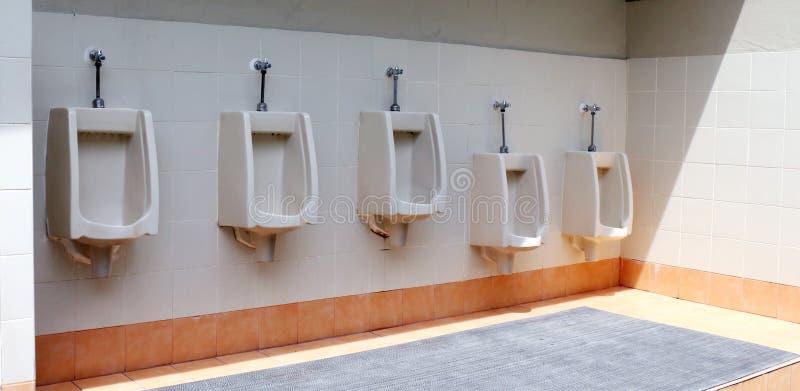 Laranja velha da cor do toalete exterior, o toalete do homem com opinião do toalete por mictórios imagens de stock royalty free