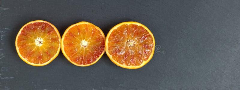 3 laranjas da metade na ardósia preta foto de stock