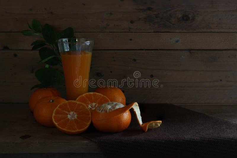 Laranjas e suco de laranjas frescos no vidro com as laranjas das partes na prancha de madeira imagem de stock royalty free