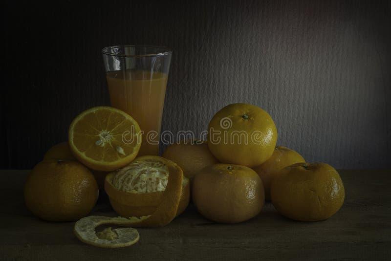 Laranjas e vidro do suco em uma tabela de madeira / Ainda fruto da vida imagem de stock