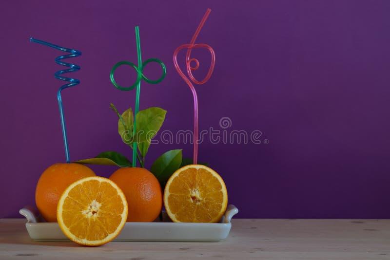 Laranjas frescas com palhas coloridas extravagantes imagem de stock royalty free