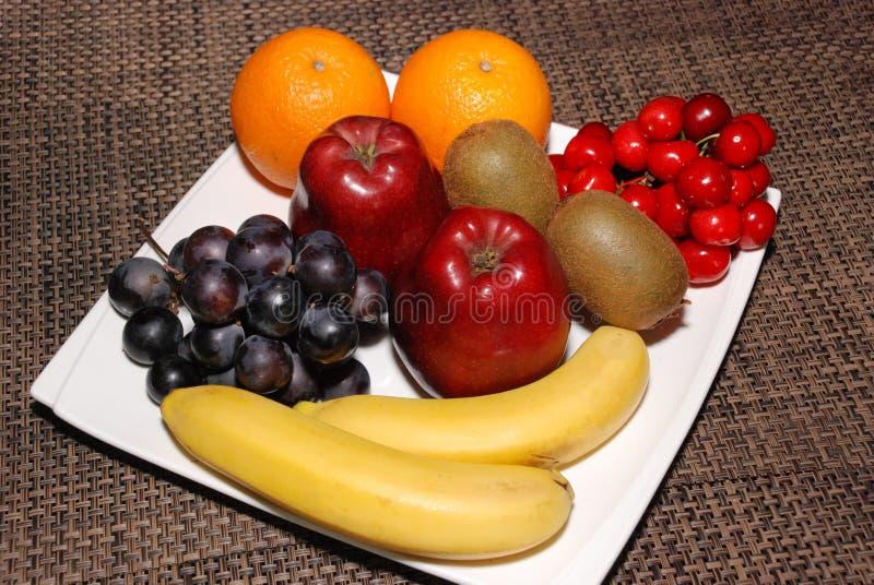 Laranjas, maçãs, uvas, quivis, cerejas, bananas na placa branca na tabela marrom fotografia de stock royalty free